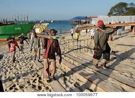 African Longshoremen Unload Lumber Boat In Port Of Zanzibar.