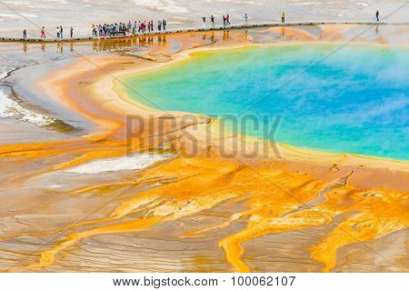 Detailed photo of Grand Prismatic Spring from above with unrecognizable tourists watching it. Yellowstone National Park, Wyoming, USA
