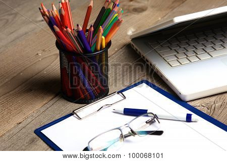 blank notebook on wooden table with pencils