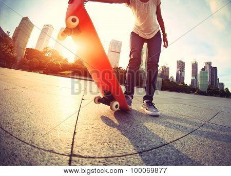 woman skateboarder with skateboard at sunrise city