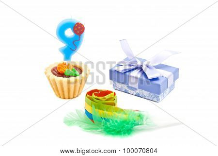 Cake With Nine Years Birthday Candle, Whistle And Gift On White