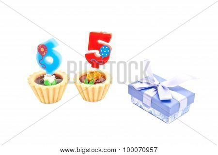 Cakes With Sixty Five Years Birthday Candles And Gift On White