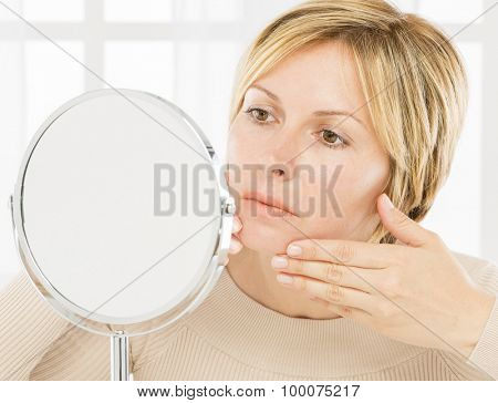 Forty years lady with short hair in front of mirror
