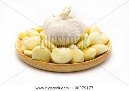 Fresh raw root garlic on wooden plate