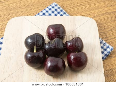 Red Plums On A Wooden Cutting Board