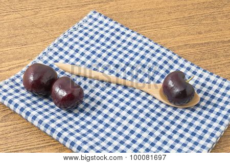 Three Red Plums On Blue Checked Napkin