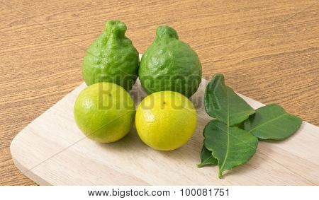 Green Kaffir Lime With Lemon Lime On Wooden Board