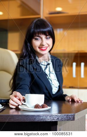 Attractive Girl Takes A Cup Of Coffee At A Table In The Office