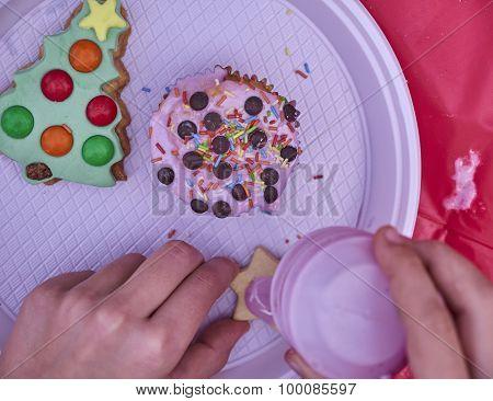 kid's hands preparing Christmas colorful cookies