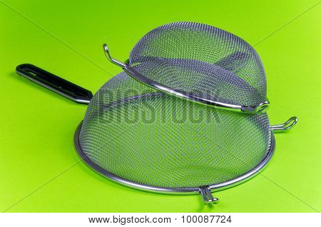 Two Kitchen Sieves And Wooden Spoon On Green Background