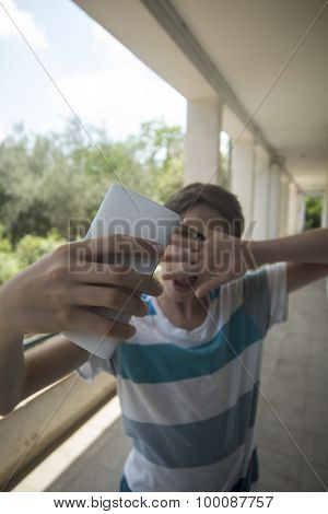 Teenage boy taking a selfie with his phone