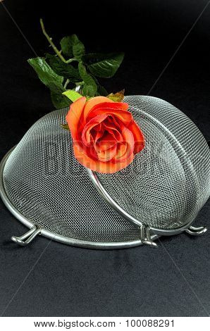 Two Kitchen Sieves With Red Rose On Black Background