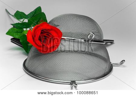 Two Kitchen Sieves With Red Rose On White Background