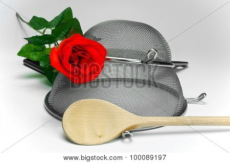 Two Kitchen Sieves With Red Rose And Wooden Spoon On Black Background