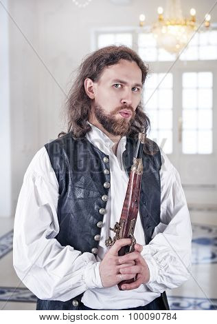 Young Handsome Man In Medieval Clothes With Pistol