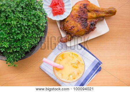 Cold tea in a glass with grilled chicken cooked hot meal with beautifully laid