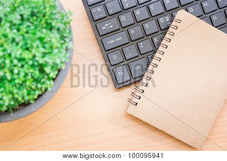 The concept composition with a black keyboard and a notebook on a wooden table beautifully vintage s