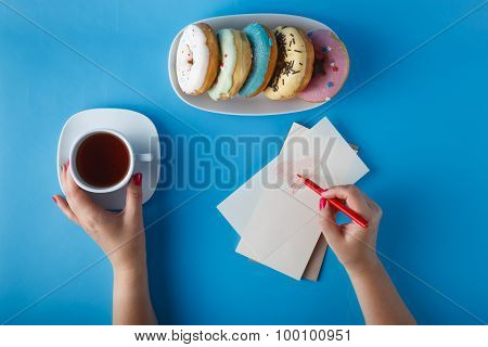 Hands Painting Heart With Tea And Donuts