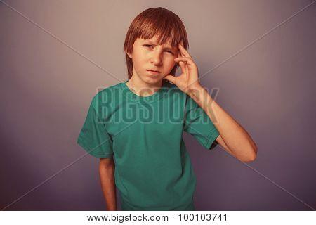 European-looking boy of ten years headache, migraine on a gray b