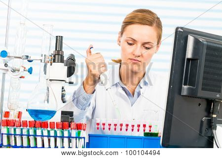 Woman in a medical lab technician with a microscope and a monitor