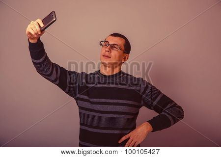 European-looking man of 30 years holding a cell phone retro