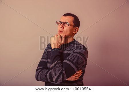 European-looking man of 30 years in  glasses,  thinking retro