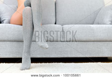 Woman With Beautiful Legs Sitting On Sofa.