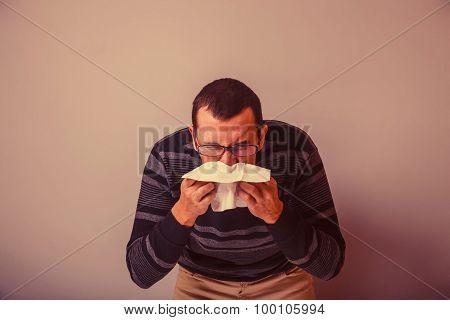 European-looking man of 30 years is sick, cold, handkerchief ret