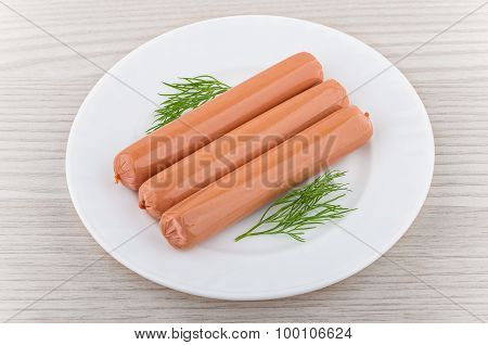 Three Sausages With Dill In Glass Plate On Table