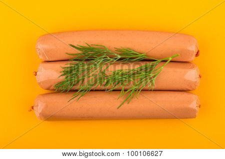 Three Sausages With Dill On Plastic Board