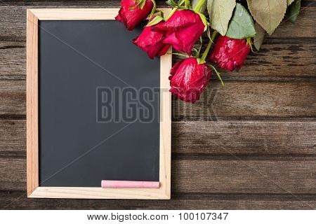 Black Board And Red Roses On Wooden Background, Top View