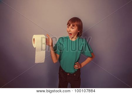 European-looking  boy of ten  years with  toilet paper on a gray