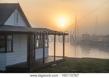 Stunning Sunrise Landscape Over River House And Foggy River