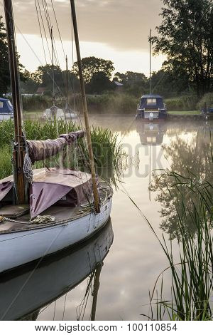 Boats Moored On Riverbank At Sunrise In Countryside Landscape