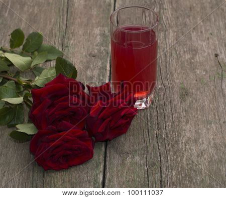 Red Glass Of Juice And Bouquet Of Red Roses