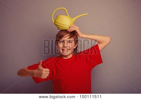 teenager boy twelve years in red shirt holding watering  can ret