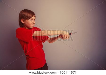 Teenager boy twelve years in the red t-shirt with knife evil Bon