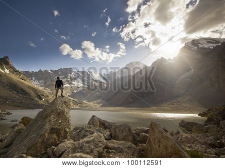 man on a cliff at sunset near the mountain lake