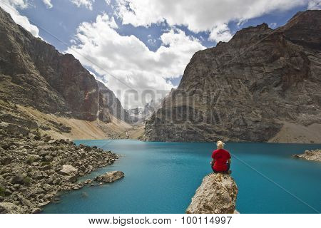 girl in red t-shirt sitting near blue mountain lake