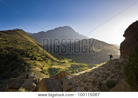 man on a cliff at sunset surrounded by green hills