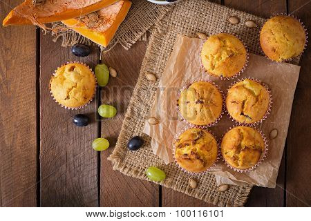 Appetizing and ruddy muffins with pumpkin and grapes