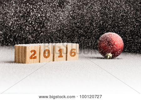 2016 Sign On Wooden Cubes And Red Christmas Ball Lying On A Snowy Surface