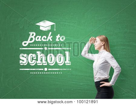 Young Schoolgirl Is Looking Through The Air. Words ' Back To School ' Are Written On The Green Chalk