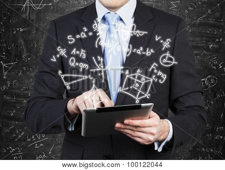 Young Man In Formal Suit Is Holding A Tablet With Math Formulas Projection On The Air.