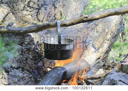 Pot Of Tea Hanging On The Stake High In The Rocks