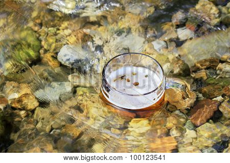 Mug Of Excellent Beer Sparkles In The Sun In A Mountain Stream