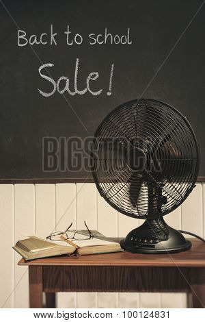 Vintage electric fan with book on table