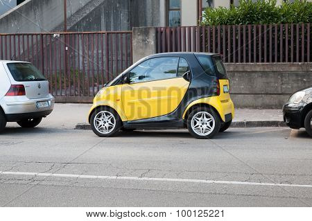 Black And Yellow Smart Car Parked On Urban Roadside