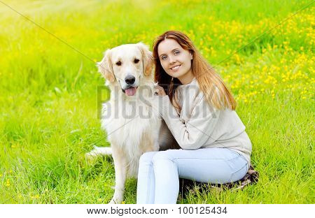 Happy Owner And Golden Retriever Dog Sitting Together On The Grass In Sunny Summer Day