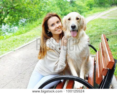 Portrait Of Happy Owner And Golden Retriever Dog Sitting Together On The Bench In City Park
